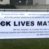 A Banner that reads Black Lives Matter has been vandalized so that black is poorly scratched out and ALL is written above it.